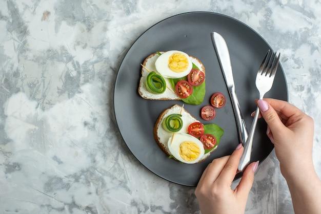 上面図おいしい卵サンドイッチとナイフとフォークの内側プレート白い背景サンドイッチダイエットランチトースト食品健康ハンバーガーパンミール