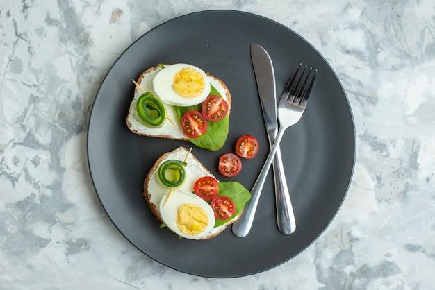 上面図おいしい卵サンドイッチとナイフとフォークの内側プレート白い表面サンドイッチダイエット健康食事ランチパンハンバーガートーストフード