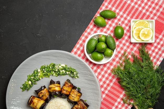 Vista dall'alto gustosi involtini di melanzane cucinati con riso e feijoa su una superficie scura che cucina un piatto di colore verde