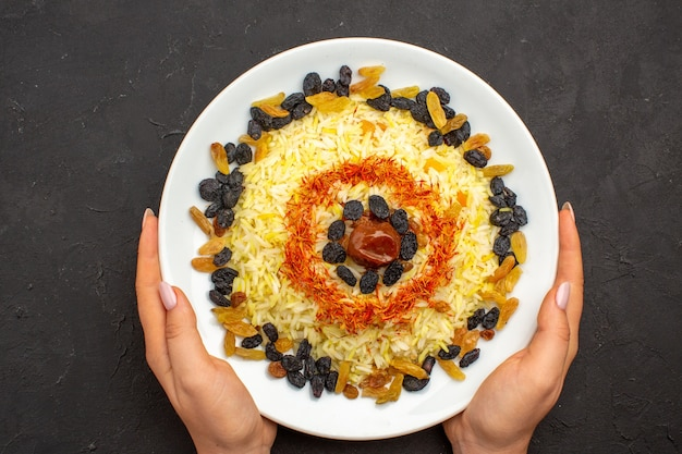 Top view tasty famous eastern meal consists of cooked rice and different raisins on dark