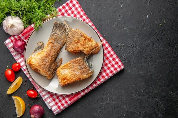 Vista dall'alto gustosa frittura di pesce su piatto grigio su tovagliolo aneto fette di limone pomodorini aglio su sfondo scuro