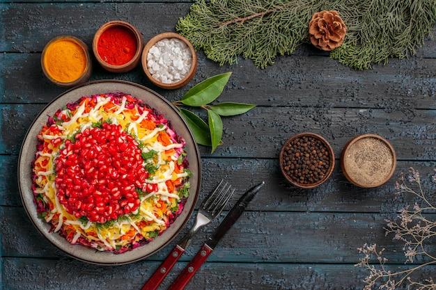 Vista dall'alto cibo gustoso appetitoso cibo natalizio e ciotole di spezie accanto ai rami di abete rosso con coltello a forchetta con coni
