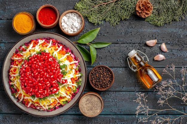 Top view tasty food appetizing christmas food and five bowls of colorful spices next to the bottle of oil garlic spruce branches with cones