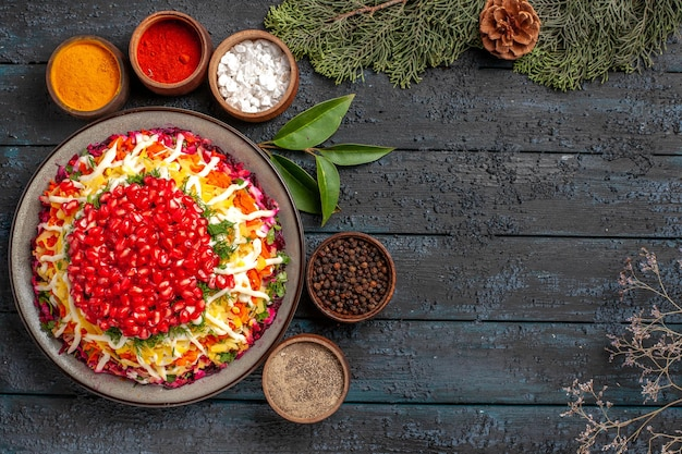 Top view tasty food appetizing christmas food and five bowls of colorful spices next to the spruce branches with cones