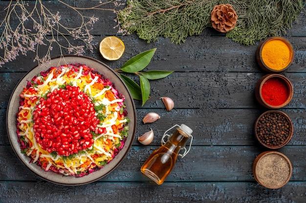 Vista dall'alto cibo gustoso cinque ciotole di spezie colorate piatto di natale aglio bottiglia di olio limone accanto ai rami di abete rosso con coni