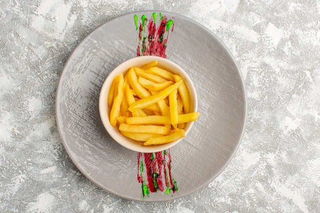 Top view of tasty french fries inside white plate on the light surface