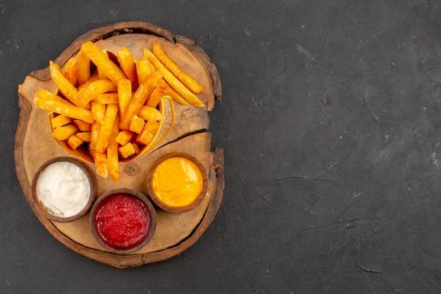 Vista dall'alto di gustose patatine fritte con salse sul tavolo nero