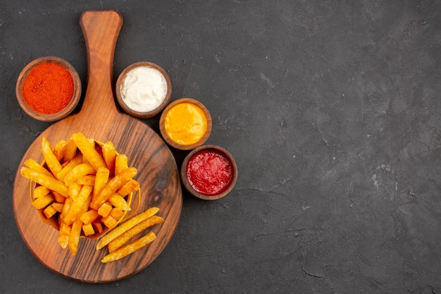 Top view of tasty french fries with sauces on black table