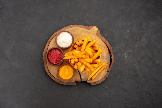 Vista dall'alto di gustose patatine fritte con salse su nero