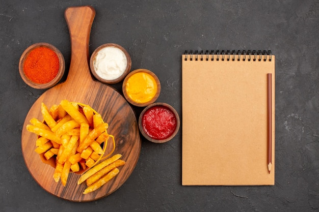 Top view of tasty french fries with sauces on black