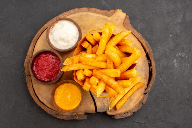 Top view of tasty french fries with sauces on dark