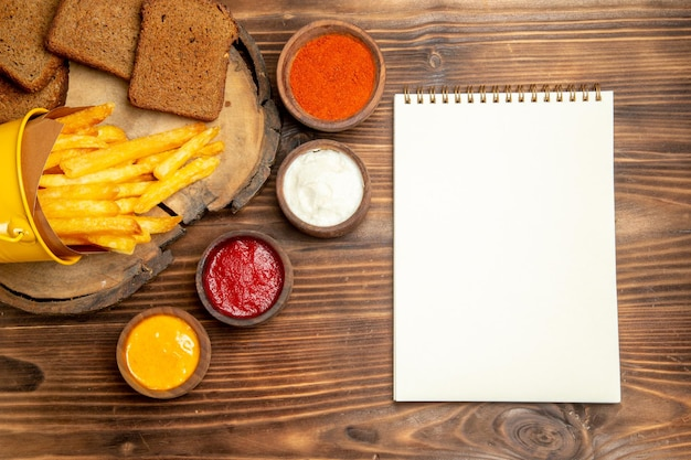 Top view of tasty french fries with seasonings on brown table