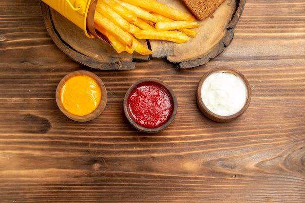 Vista dall'alto di gustose patatine fritte con condimenti sul tavolo marrone