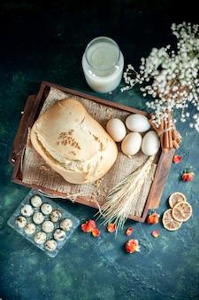 トップビュー暗い背景に卵と牛乳とおいしい焼きたてのパンケーキパイ茶砂糖パン焼きビスケット朝食生地