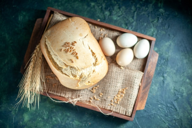 Top view tasty fresh bread with eggs on dark background cake pie tea sugar biscuit bun bake dough