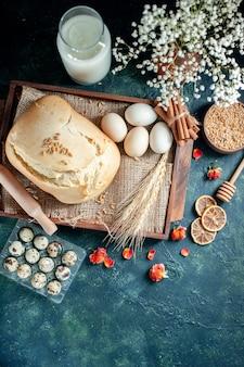 Vista dall'alto gustoso pane fresco con uova e latte su sfondo scuro torta torta tè zucchero panino biscotto colazione pasta cuocere
