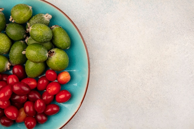 Top view of tasty fresh feijoas with cornelian cherries on a blue dish on a grey background with copy space