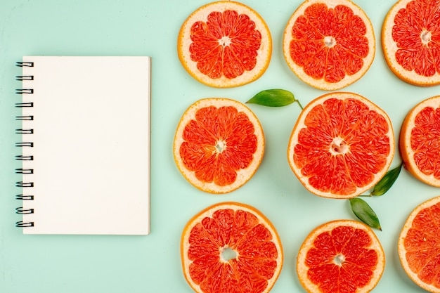 Top view of tasty fresh grapefruits lined on light-blue surface