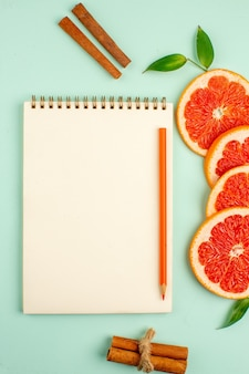 Top view of tasty fresh grapefruits with notepad on the light-blue surface