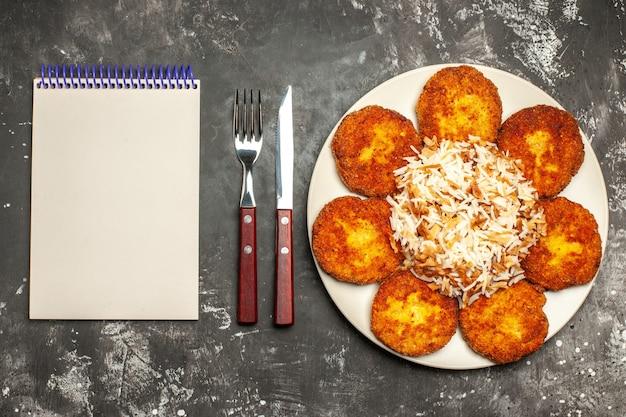 Vista dall'alto gustose cotolette fritte con riso cotto su carne di piatto foto pasto superficie scura