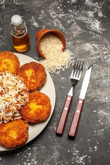 Vista dall'alto gustose cotolette fritte con riso cotto su carne di foto di farina di superficie scura
