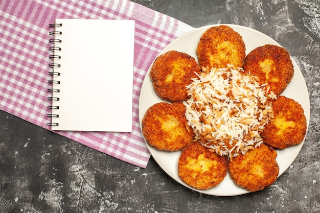 Top view tasty fried cutlets with cooked rice on a dark surface rissole meat food