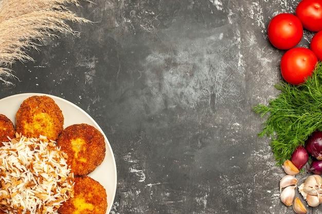 Вид сверху вкусные жареные котлеты с вареным рисом на серой поверхности блюдо фото мясо