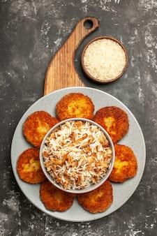 濃い灰色の表面の肉のリッソール皿にご飯と一緒においしい揚げカツレツの上面図