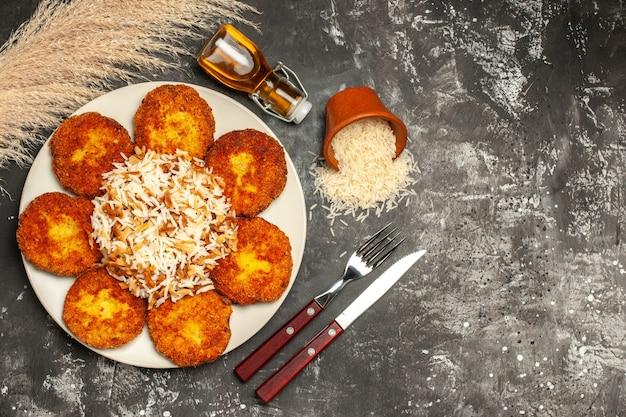 Вид сверху вкусные жареные котлеты с вареным рисом на темной поверхности блюдо фото мясо
