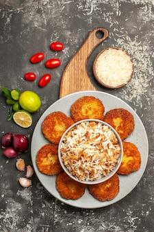 Вид сверху вкусные жареные котлеты с вареным рисом на темной поверхности мясной котлеты