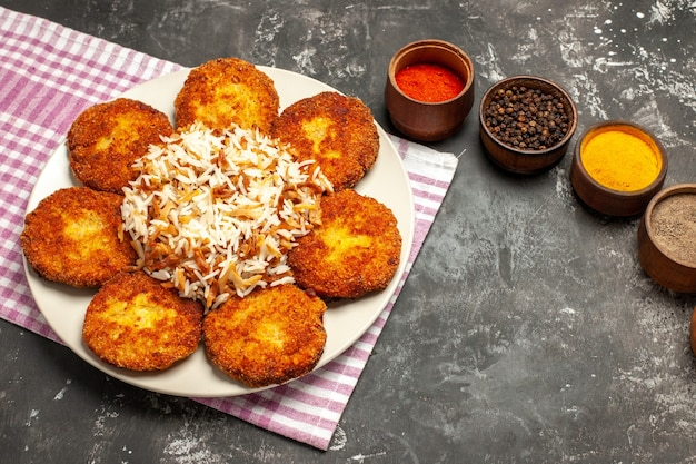 Top view tasty fried cutlets with rice and seasonings on dark floor food meat rissole