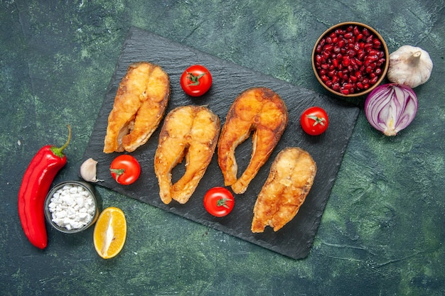 Top view of tasty fried fish with red tomatoes, garlic, lemon and red pepper