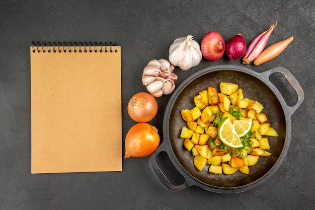 Top view of tasty fried potatoes inside pan with lemon and garlics around on dark surface
