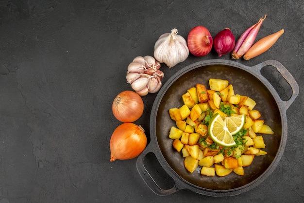 Vista dall'alto di gustose patate fritte all'interno della padella con limone e garlics intorno sulla superficie scura