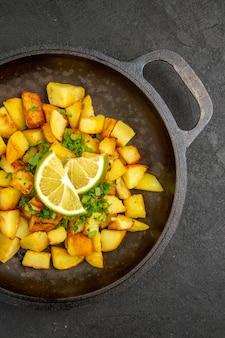 Vista dall'alto di gustose patate fritte all'interno della padella con fette di limone sulla superficie scura
