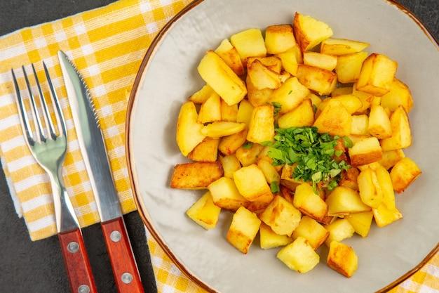 Vista dall'alto di gustose patate fritte all'interno del piatto sulla superficie grigio scuro