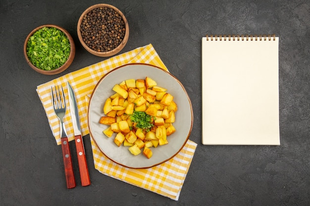 Top view of tasty fried potatoes inside plate with greens on a dark-grey surface