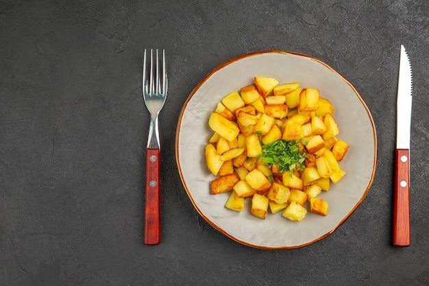 Vista dall'alto di gustose patate fritte all'interno del piatto con verdure sulla superficie scura