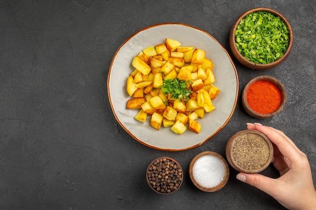 Vista dall'alto di gustose patate fritte all'interno del piatto con condimenti sulla superficie scura