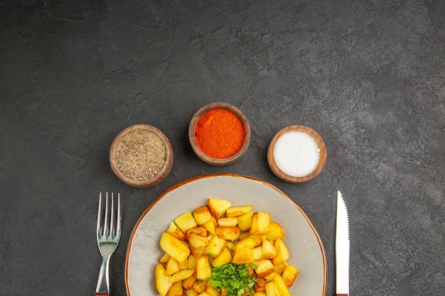 Top view of tasty fried potatoes inside plate with seasonings on the dark surface