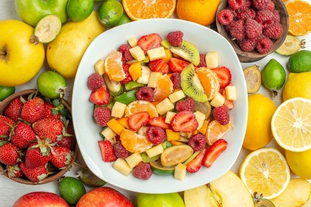 Vista dall'alto gustosa macedonia con frutti diversi su sfondo bianco