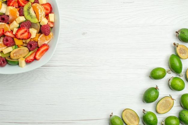 Top view tasty fruit salad with fresh feijoas on white desk