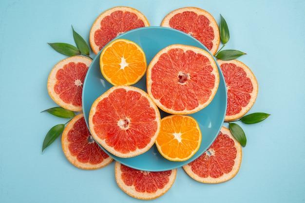 Vista dall'alto di gustosi pompelmi fette di frutta sulla superficie blu