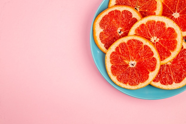 Top view of tasty grapefruits fruit slices inside plate on a pink surface
