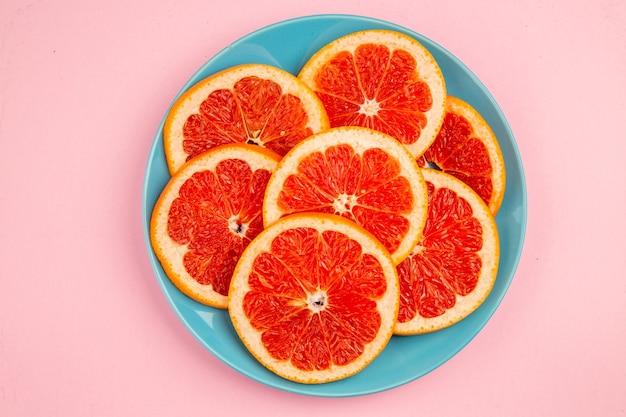 Vista dall'alto di gustosi pompelmi fette di frutta all'interno del piatto sulla superficie rosa