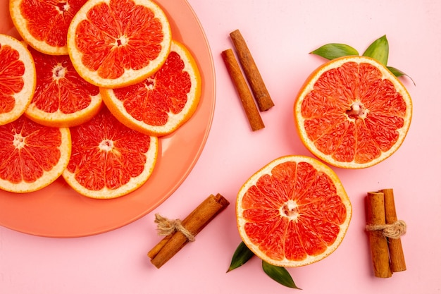 Top view of tasty grapefruits fruit slices on pink surface