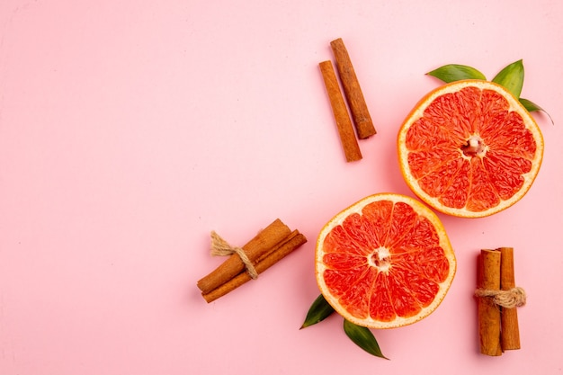 Top view of tasty grapefruits fruit slices on the pink surface