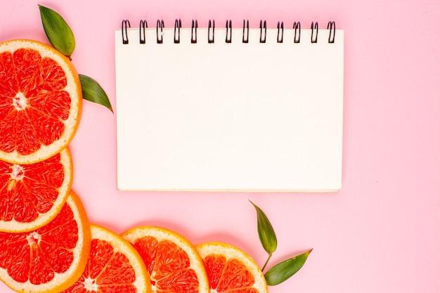 Vista dall'alto di fette di frutta succosa gustosi pompelmi sulla superficie rosa