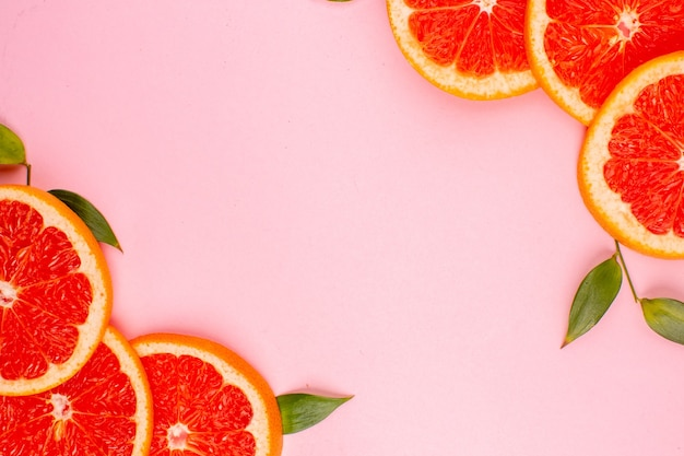 Top view of tasty grapefruits on pink surface