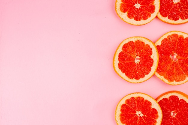 Top view of tasty grapefruits sliced juicy fruits on light pink surface